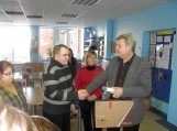 """UAB """"Šilutės būstas"""" vadovas Aleksas Kvederis centro lankytojams padovanojo naują nešiojamą kompiuterį. Nuotraukos Edvardo Lukošiaus"""