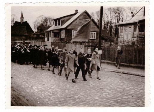 1962 m. vidurinės mokyklos mokiniai ir mokytojai žygiuoja į karių kapines.