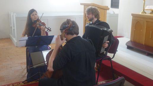 Žemaičių Naumiesčio evangelikų bažnyčioje koncertuoja (iš kairės): D. Dėdinskaitė, T. Motiečius ir G. Pyšniak. Nuotrauka muziejaus