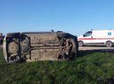 Moters vairuojamas automobilis nuslydo nuo kelio ir apsivertė