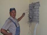 Statybininkas rodo elektros instaliacijos skydinėje antrame aukšte atrastą kabelį, kuriuo buvo vagiama elektra