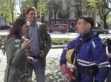 Arnoldą Sirvydį kalbina žurnalistė. Šalia stovi kunigas Remigijus Šemeklis