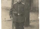 Pirmojo pasaulinio karo kareivis iš Saugų apyl., su pilna apranga, dešinėje rankoje laiko prie šono prispaustą šautuvą.
